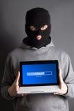 Hombre enmascarado con el ordenador del cargamento sobre gris Imagenes de archivo