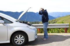 Hombre enojado con el coche de la ruptura Fotos de archivo