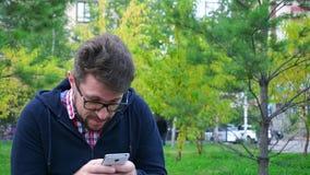Hombre enojado con una barba que se sienta en el parque Escribe mensajes en teléfono almacen de metraje de vídeo