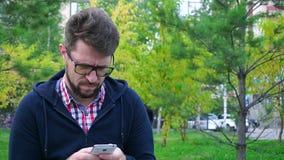 Hombre enojado con una barba que se sienta en el parque Escribe mensajes en teléfono almacen de video
