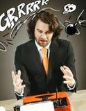 Hombre enojado con una máquina de escribir pasada de moda Foto de archivo libre de regalías