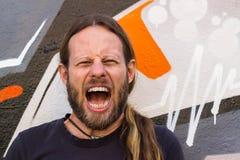 Hombre enojado, de griterío contra la pared de la pintada. foto de archivo