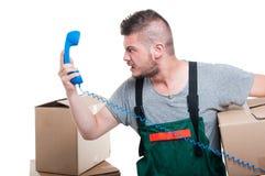 Hombre enojado del motor que sostiene la caja de cartón y el receptor de teléfono Imagen de archivo