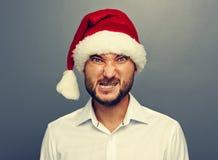 Hombre enojado en el sombrero de santa sobre gris Foto de archivo
