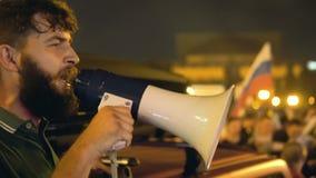 Hombre enojado en la revolución en la noche con grito del megáfono Revolucionario en la noche almacen de metraje de vídeo
