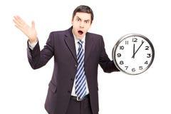 Hombre enojado en un traje que celebra un reloj y gesticular Imagen de archivo