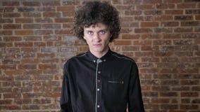 Hombre enojado joven con el pelo rizado que mira la cámara, furiosa, fondo de la pared de ladrillo metrajes