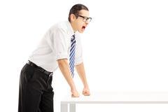 Hombre enojado joven en una griterío de la tabla Imagen de archivo
