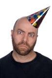 Hombre enojado que desgasta un sombrero del partido Foto de archivo libre de regalías