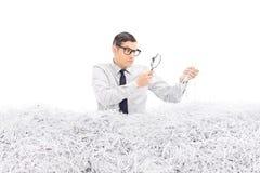 Hombre enojado que examina una pila de papel destrozado Fotos de archivo