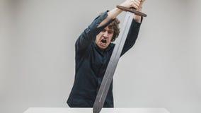 Hombre enojado que golpea su escritorio con una espada Fotografía de archivo libre de regalías