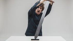 Hombre enojado que golpea su teléfono con una espada Fotos de archivo libres de regalías