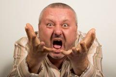 Hombre enojado que grita en la cámara que señala con las manos Imagen de archivo libre de regalías