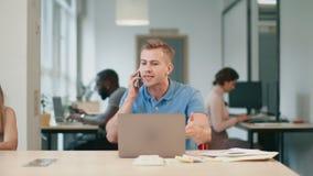 Hombre enojado que habla en móvil en el espacio coworking Hombre agresivo que tiene llamada de teléfono almacen de metraje de vídeo
