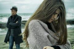 Hombre enojado que mira a la novia triste después de lucha delante del tiro medio del océano Fotografía de archivo libre de regalías