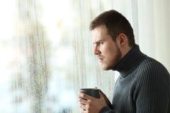 Hombre enojado que mira a través de una ventana en un día lluvioso Imagen de archivo libre de regalías
