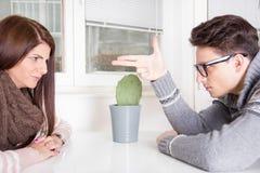 Hombre enojado que señala en la mujer que se sienta a través de la tabla Imágenes de archivo libres de regalías