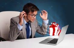 Hombre enojado que se sienta en el escritorio y que mecanografía en el ordenador portátil con el actual boxe Fotos de archivo