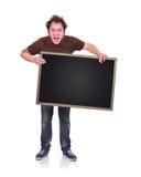 Hombre enojado que sostiene la pizarra Imagen de archivo