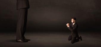 Hombre enorme con el pequeño hombre de negocios que se coloca en el concepto delantero Foto de archivo libre de regalías