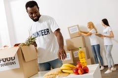 Hombre entusiasta hermoso que ayuda como voluntario Foto de archivo libre de regalías