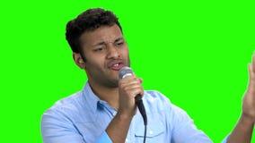 Hombre entusiasta que canta con el micrófono en la pantalla verde almacen de metraje de vídeo
