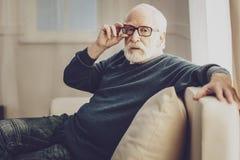 Hombre envejecido agradable que fija sus vidrios imagen de archivo
