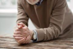 Hombre envejecido agradable que pone las manos en la tabla Fotografía de archivo