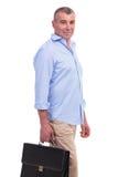 Hombre envejecido centro casual que sostiene una maleta Foto de archivo libre de regalías