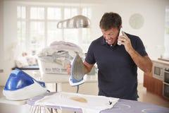 Hombre envejecido centro distraído por el teléfono cuando el planchar quema la camisa imagen de archivo