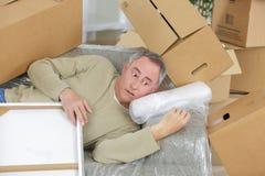 Hombre envejecido centro en medio de las cajas precarias de las pilas imagen de archivo