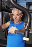Hombre envejecido centro que usa la máquina de los pesos en gimnasio imagen de archivo