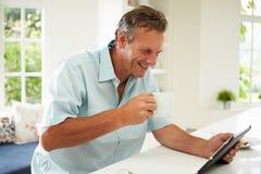 Hombre envejecido centro que usa la tableta de Digitaces sobre el desayuno imagenes de archivo