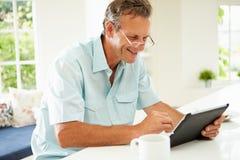 Hombre envejecido centro que usa la tableta de Digitaces sobre el desayuno Imágenes de archivo libres de regalías