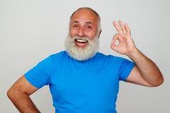 Hombre envejecido con la barba blanca y la sonrisa amplia que muestran gesto ACEPTABLE fotos de archivo libres de regalías