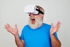 Hombre envejecido en VR-auriculares sorprendido por la imagen en reali virtual foto de archivo