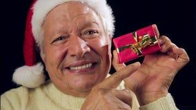 Hombre envejecido feliz que ofrece un regalo envuelto pequeño rojo metrajes