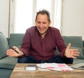 Hombre envejecido medio acertado con las hojas de paga, las facturas y las finanzas de la contabilidad de ordenador felices libre fotografía de archivo