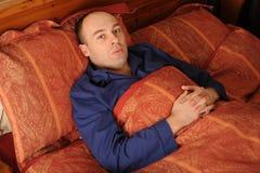Hombre envejecido medio en cama Fotos de archivo libres de regalías