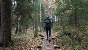 Hombre envejecido medio en un sendero ecológico a través de un bosque del otoño en un parque natural metrajes