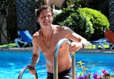 Hombre envejecido medio hermoso que sube fuera de piscina Imagenes de archivo