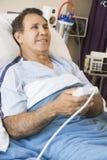 Hombre envejecido medio que miente en cama de hospital Imagen de archivo