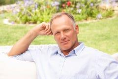 Hombre envejecido medio que se relaja en jardín imagen de archivo