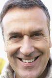 Hombre envejecido medio que sonríe en la cámara fotografía de archivo libre de regalías