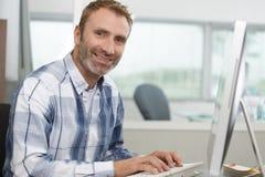 Hombre envejecido medio usando el ordenador en lugar de trabajo imágenes de archivo libres de regalías