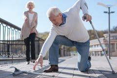 Hombre envejecido que cae su muleta en el camino Imagenes de archivo
