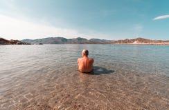 Hombre envejecido que mira el horizonte la playa dentro del agua - Sar Imágenes de archivo libres de regalías