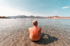Hombre envejecido que toma resto en el mar en Italia - Cerdeña Imagenes de archivo
