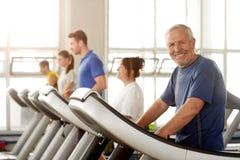 Hombre envejecido sonriente que ejercita en el gimnasio imágenes de archivo libres de regalías