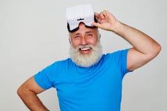 Hombre envejecido sonriente satisfecho por el trabajo de las auriculares de la realidad virtual imagen de archivo